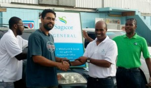 Operator of the Miniya's supermarket chain, Hilkiah Lavinier is among the commercial clients having claims settled by Sagicor General. Here he receives a cheque from Sagicor General's Assistant Vice-President of Claims, John Chandler
