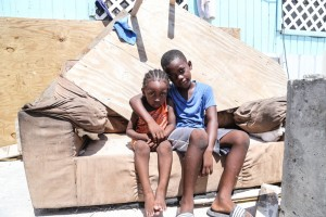 Brothers sit on a sofa outside their home, which was severely damaged by Hurricane Irma in Grand Turks, Turks and Caicos Islands.